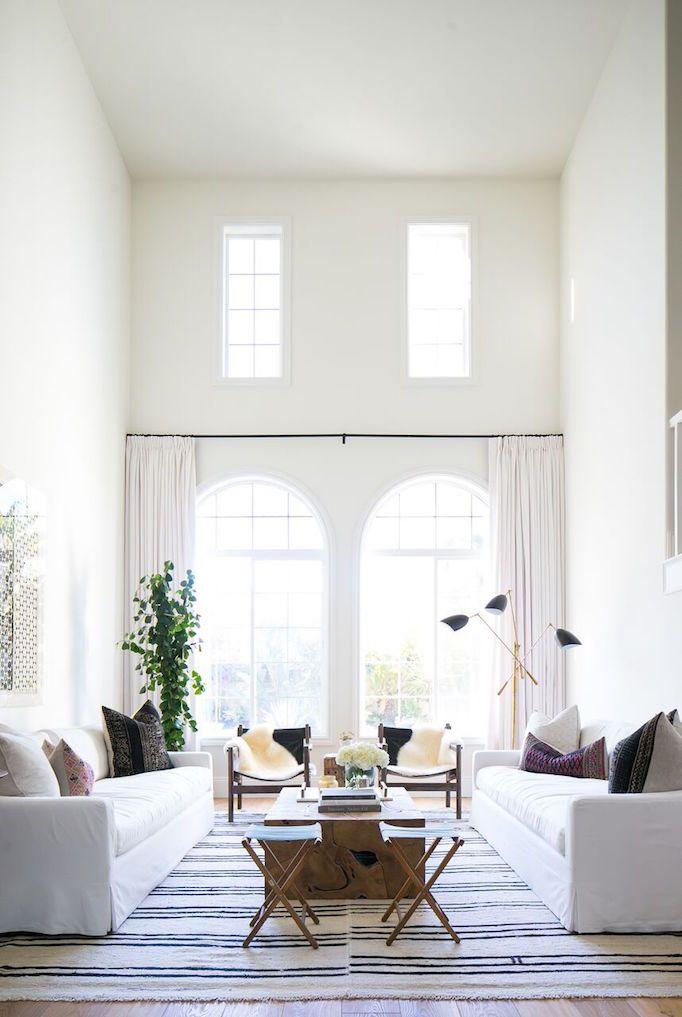 coastal bohemian living room idea white sofa custom draperies in white striped area rug mediterranean style windows light wood floors