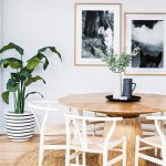 Contemporary Dining Space Round Shaped Woven Rug Round Top Wood Dining Table White Finish Dining Chairs Houseplant With Striped Pot