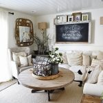 Farmhouse Rustic Living Room Idea White Shiplap Ceilings Dark Wood Floorings Wood Round Top Coffee Table White Couch White Upholstered Armchair Chalkboard Wall Decoration