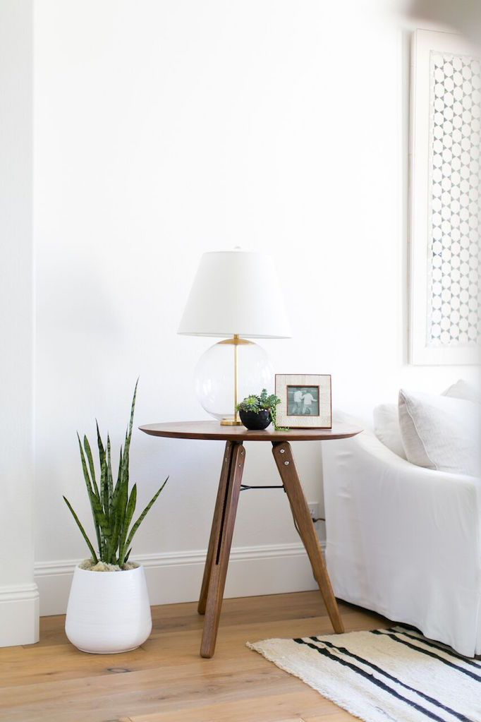 folding x base wood side table minimalist table lamp with glass ball structure and white lampshade white potted houseplant white sofa slipcover striped textile rug light wood floors