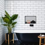 Industrial Bathroom Design With Modern Touch Claw Foot Bathtub White Subway Tiles Walls Black Hexagon Tiles Floors Recessed Shelf With Monochromatic Hexagon Highlights Wooden Side Table Potted Gr