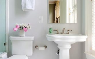 light gray walls white pedestal sink with faucet white toilet gray patterned tiles floors
