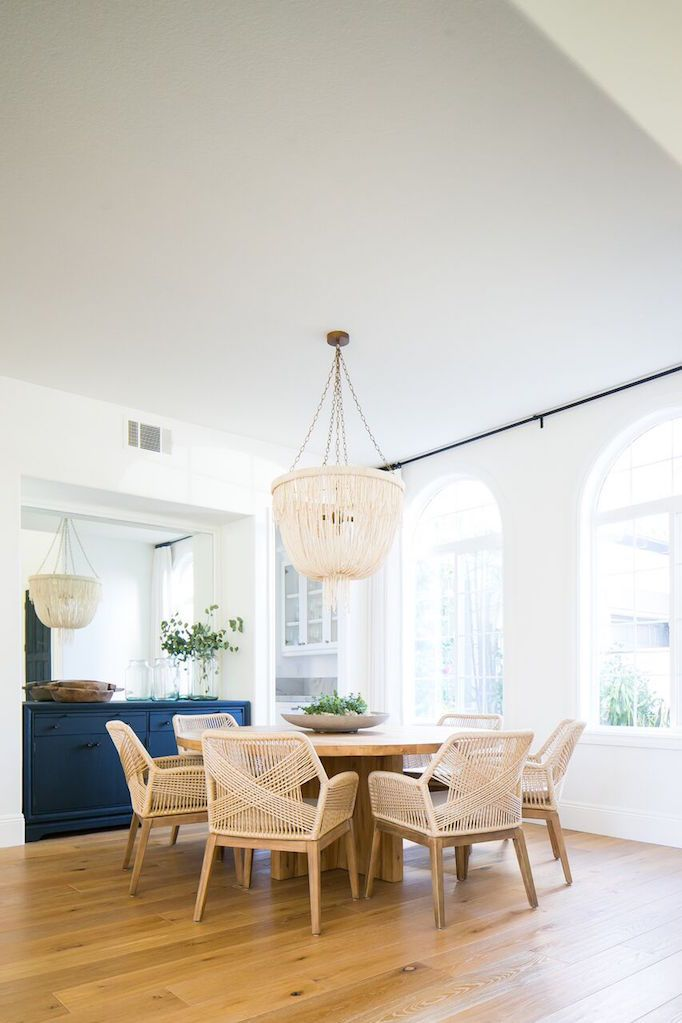 light wood dining furniture set grand chandelier in broken white navy blue kitchen cabinetry light wood floors