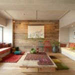 Modern Bohemian Living Room Colorful Floor Seat Wooden Coffee Table Recessed Bench Seat Multicolored & Multipatterned Throw Pillows Light Wood Floors Wood Paneling Behind The Colorful Chairs
