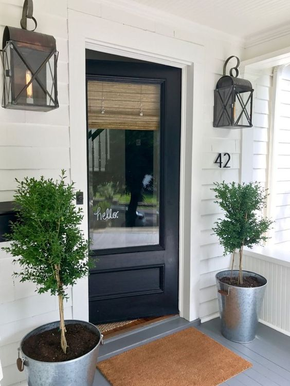 modern farmhouse exterior black painted front door wood siding exterior walls a pair of industrial style wall lamps a pair of potted houseplants woven door mat