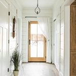 Modern Farmhouse Hallway White Pallet Walls Wood Front Door With Clear Glass Panel White Door Curtains Black Wrought Iron Light Fixtures Potted Houseplant
