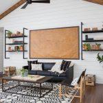 Modern Farmhouse Living Room Black Leather Sofa Black Coffee Table Monochromatic Area Rug Industrial Style Wall Racks Decorative Wall Board Dark Wood Floors White Siding Interior Walls