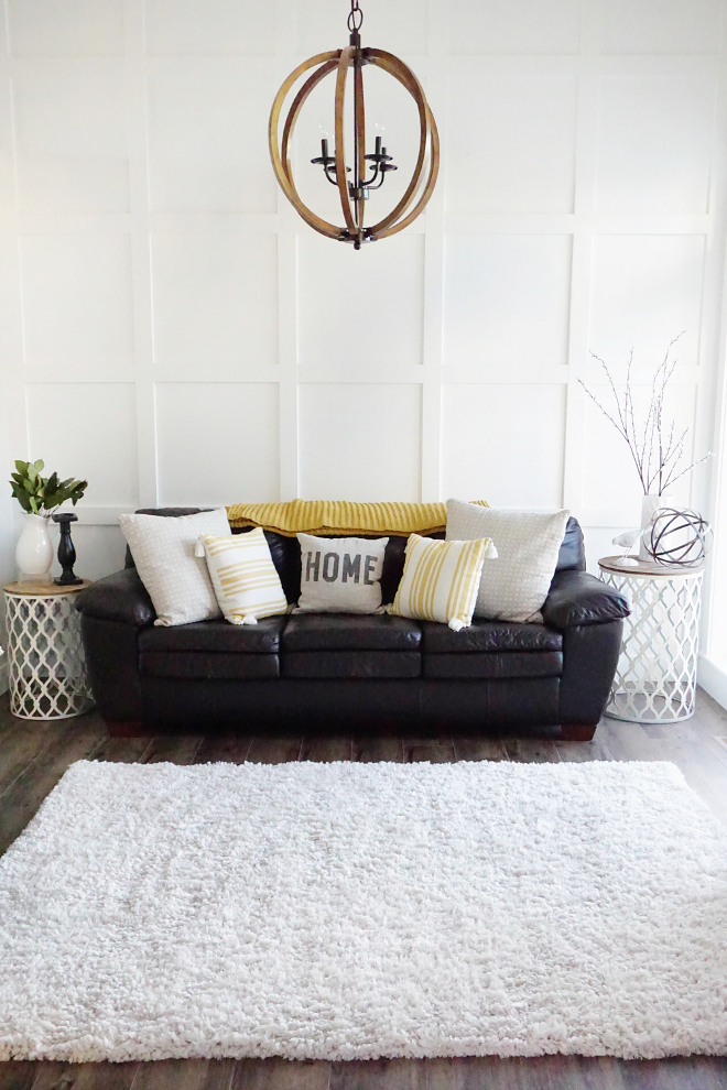modern farmhouse living room black leather sofa with white throw pillows white shag rug dark wood floors a pair of twin side tables with round top creative pendant