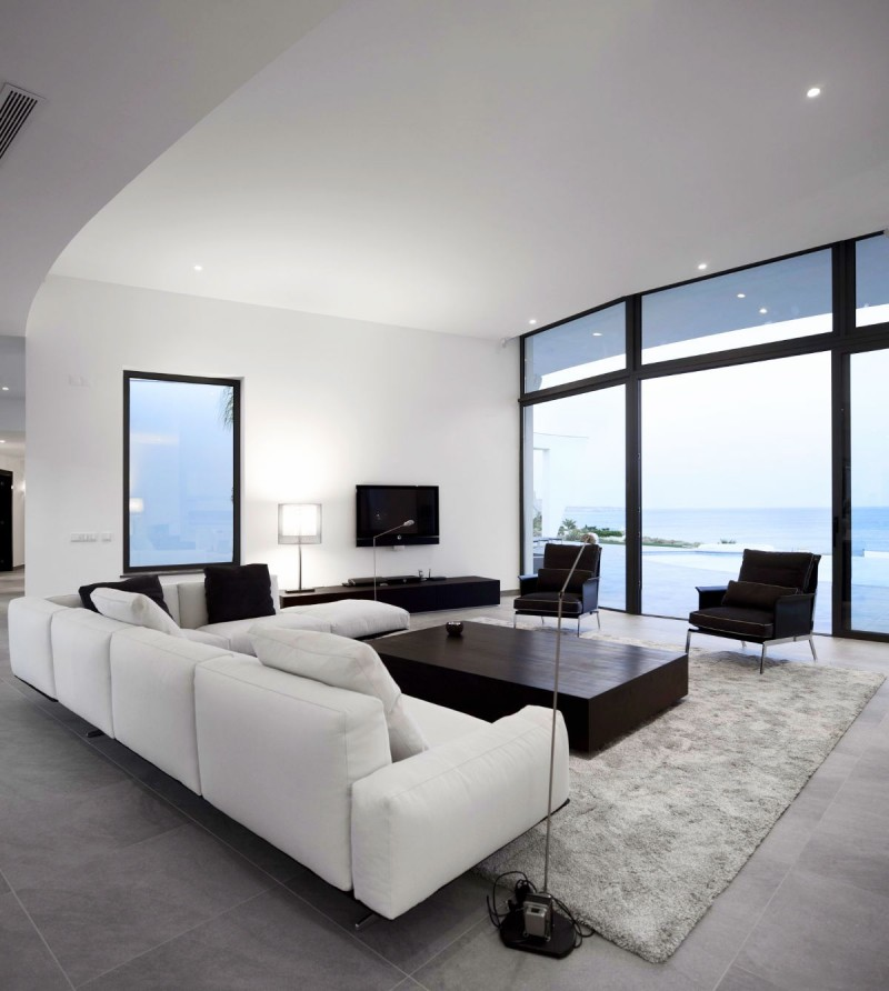 modern minimalist living room in black and white light gray area rug large glass windows minimalist white sofas minimalist black coffee table