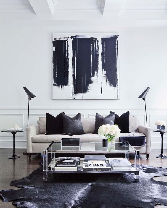 moderrn black white living room design white sofa black throw pillows glass coffee table twin side tables twin floor lamps abstract paint in white black black cowhide rug