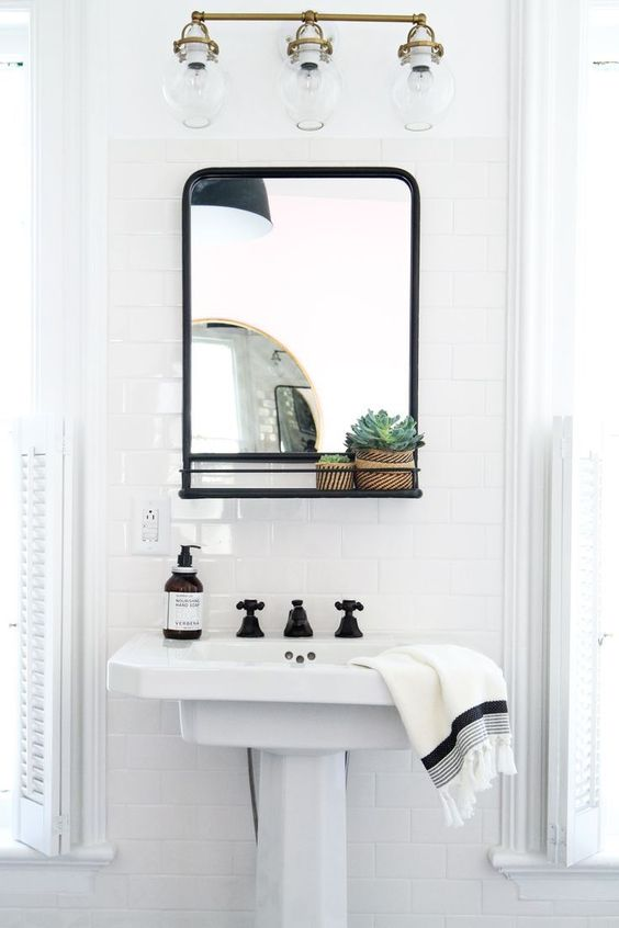 pedestal sink in white black framed mirror white ceramic tiles walls