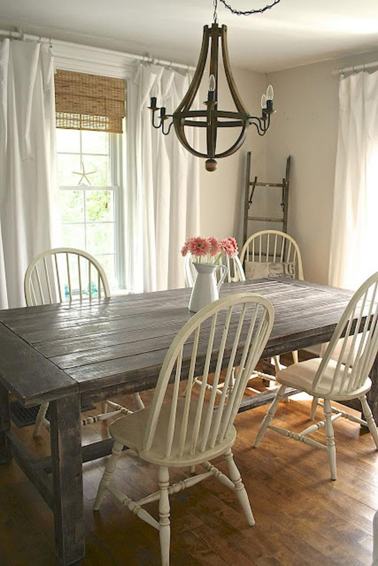 rustic dining space dramatic white drapes rough wooden table shabby white dining chairs rustic style chandelier wooden floors