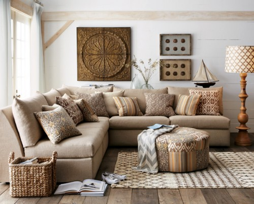 rustic farmhouse living room L shaped couch in soft cream patterned pouf table in neutral patterned area rug woven basket