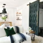 Rustic Farmhouse Living Room Idea Modern Barn Door With Modern Door Pull White Couch With Striped Blanket Green Throw Pillow Wooly White Rug Wood Top Side Table With Thin Metal Stick Legs
