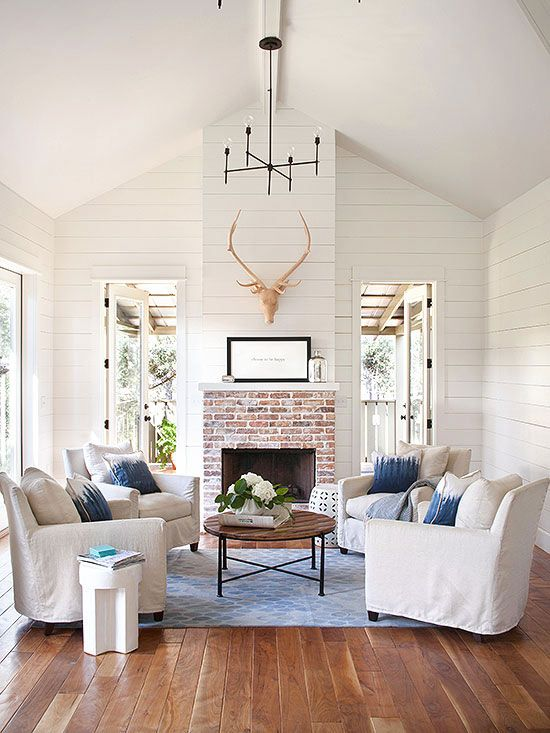 rustic farmhouse living room white chairs with blue throw pillows round wood top coffee table centered fireplace with brick surround white wood siding walls decorative deer head wood board floors