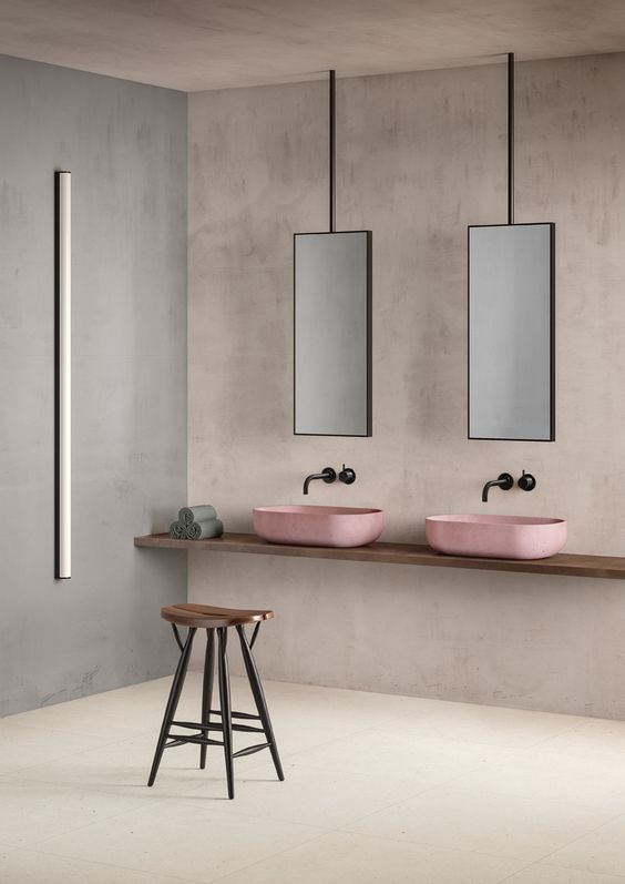 ultra modern and clean bathroom vanity with double pink sinks and wall mounted faucets a couple of vanity mirrors smooth concrete surface walls limestone floors