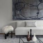 Ultra Modern Black And White Living Room Idea White Sofa With Tiny Metal Legs Glass Coffee Table With Black Accent Lines Grand Abstract Art On Wall