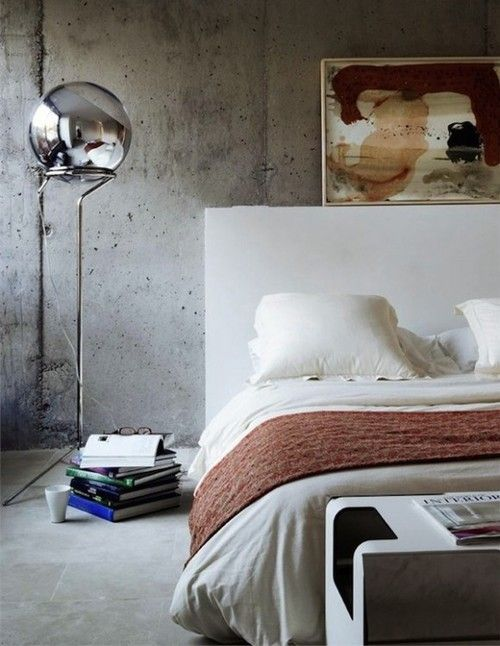 urban industrial bedroom design hard textured concrete walls concrete floors modern floor lamp with glossy ball headlamp white bed frame with higher headboard white bedding treatment