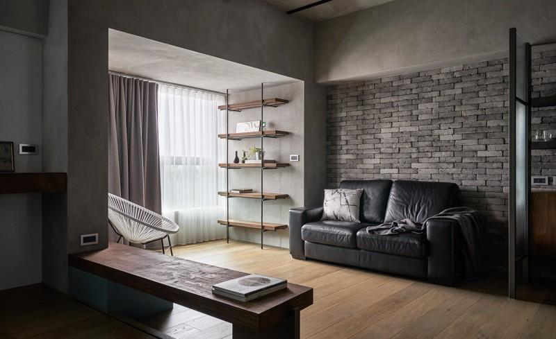 urban industrial open space industrial style rack concrete walls and ceilings gray bricks walls light wood floors integrated wood bench black leather sofa