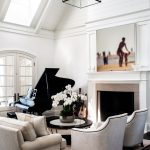 White Sofas With Black Line Accents Grand Piano In Black Creative Light Fixture With Glass Lampshade Lofted Ceilings In White Skylight