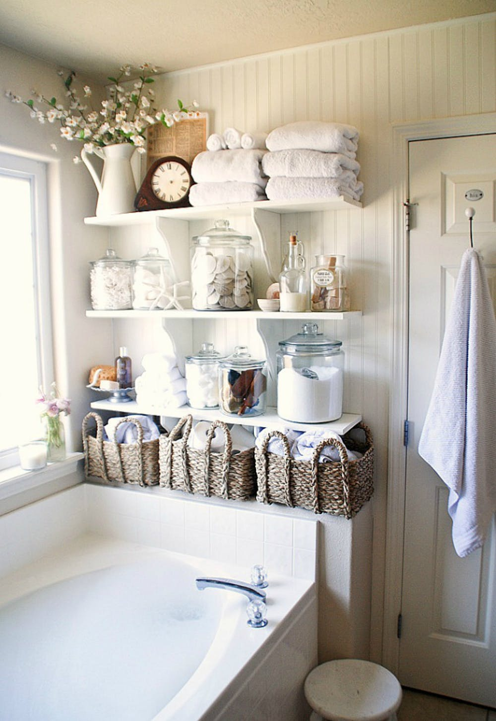 Hygge inspired bathroom open shelves in white woven baskets for towels scented salts on pots white bathtub