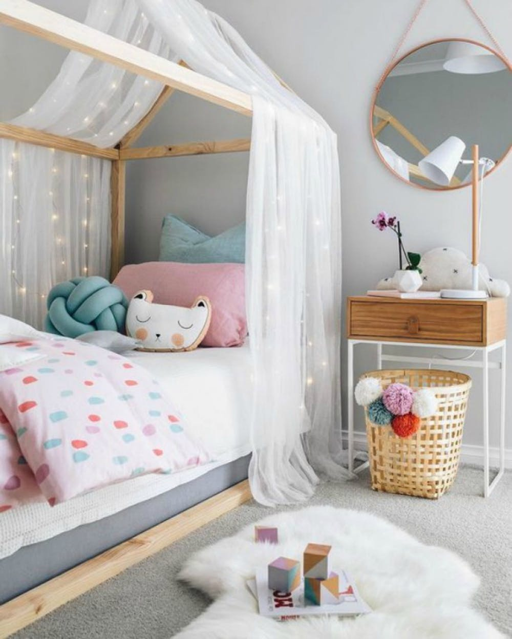 Hygge inspired kids room with canopy bed white semitransparent curtains string lights white fur rug woven basket with colorful pom pom