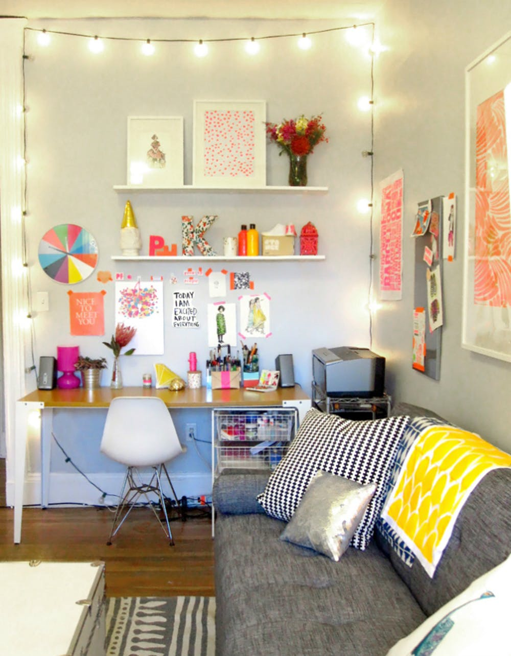 Hygge inspired workspace string lights wood top working desk Scandi style working chair in white gray sofa wood floors