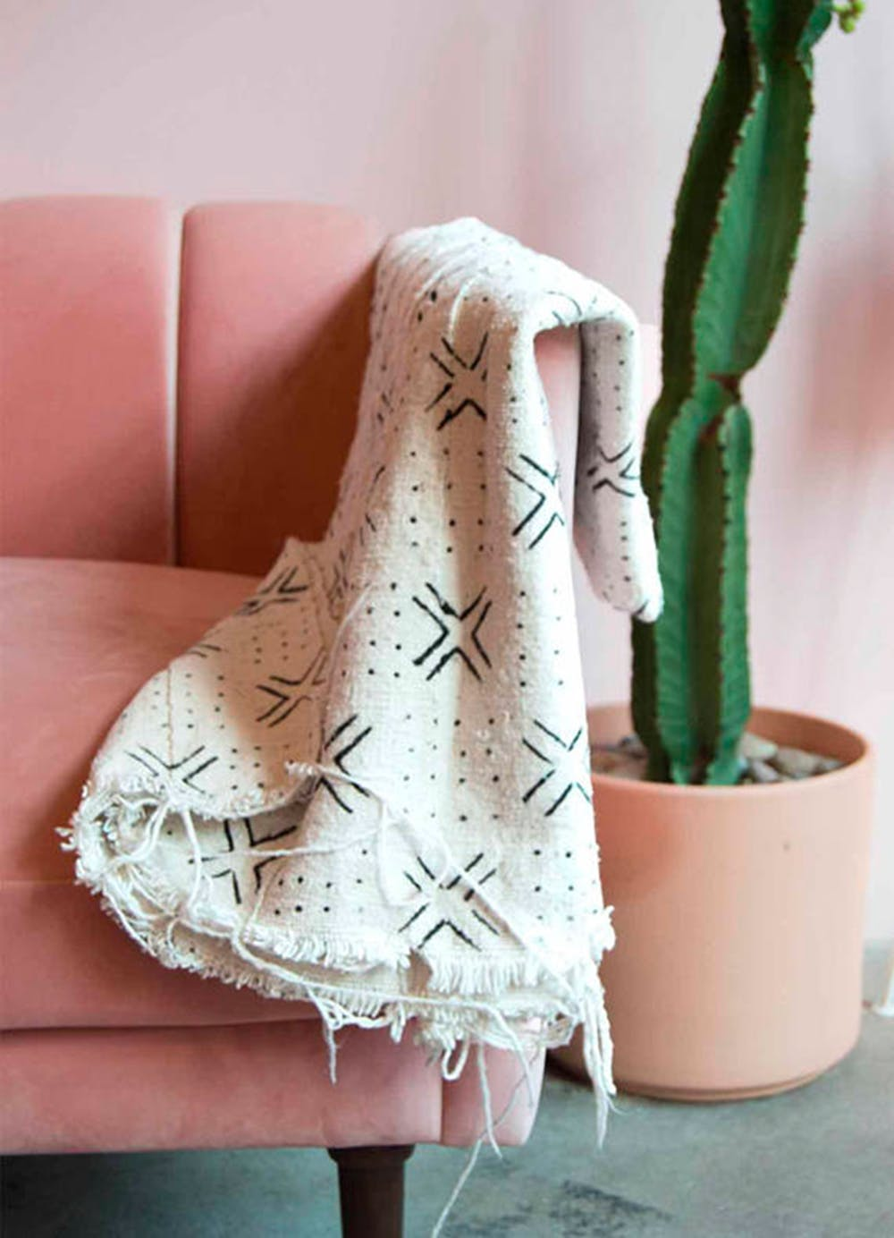Hygge style seating area soft pink seat mudcloth throw blanket in white accented with crosses & dots