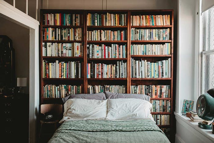 a bedroom library idea with bookcase as the headboard