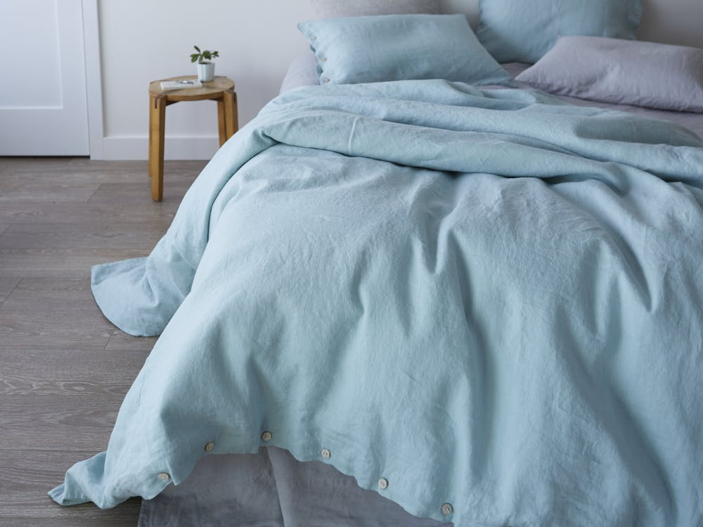 aqua duvet cover with wooden button detail aqua pillow cases storm toned bed linen wood bedside table