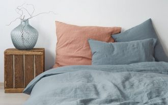 bed linen product from Linen Tales huge pillow in pastels blue duvet with wooden buttons crate bedside table glass vase
