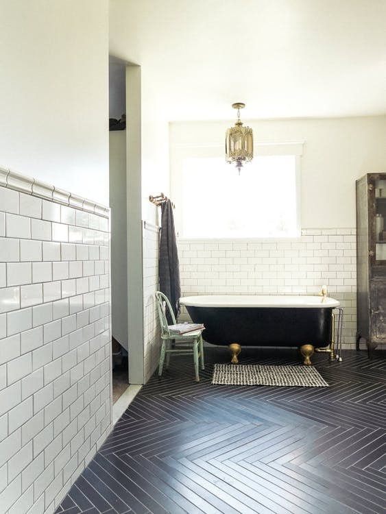 black herringbone tile floors white subway tile walls classic bathtub in white black striped bathroom mat