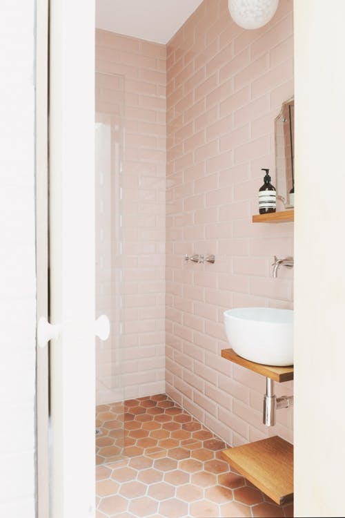 blush pink subway tile walls darker brown hexagon tile floors floating bathroom sink with wooden countertop