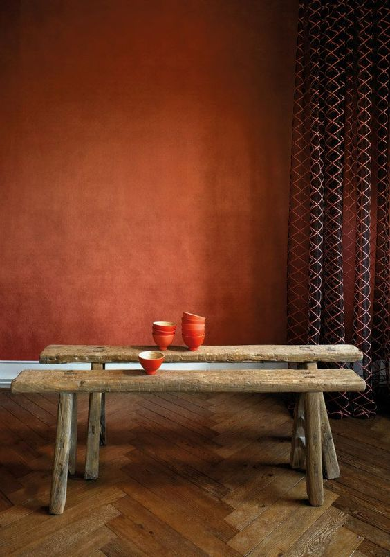 copper like wallcovering deep brown curtains with symmetrical patterns rustic bench seats herringbone tile floors