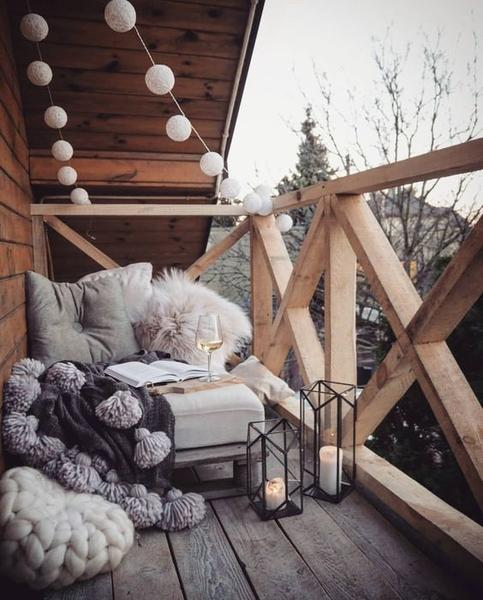 cozy balcony idea comfy beanbag in light grey fury throws ottoman table glass candle stands string lightings in white wooden railing system