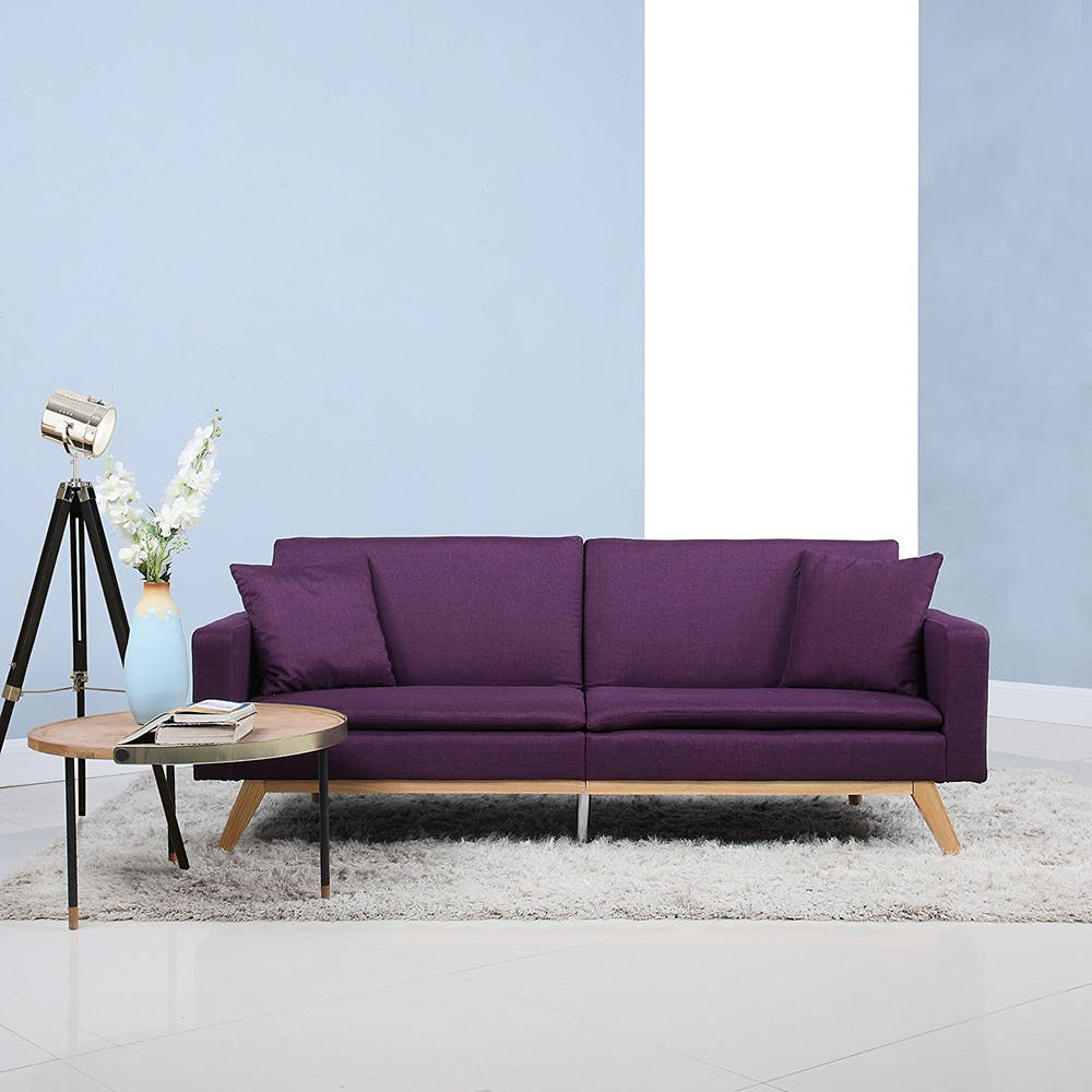 deep purple futon cushion with wood frame round top coffee table tripod floor lamp wooly area rug in white