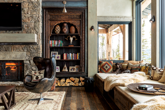 fireplace surround the seating area some logs under classic bookcase dark leather chair furry blankets hardwood bench seat wood board floors stoned walls multicolored throw pillows