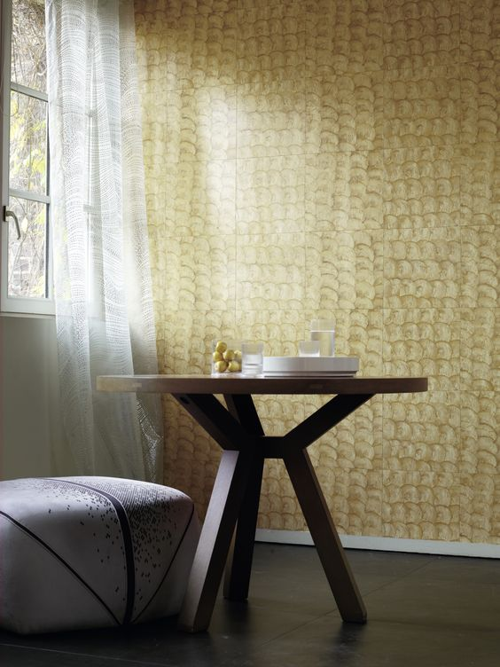 gold shells wallcovering product dramatic white curtains white ottoman chair with dark accent lines round top table with angled legs