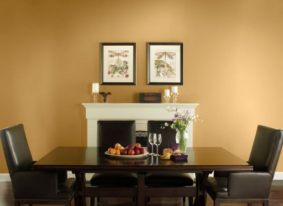 gold toned wall paint black leather dining chairs dark toned dining table a couple of wall art with black frame