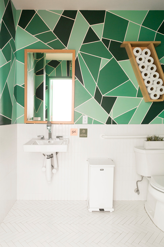 herringbone patterned tile floors in white wall mounted bathroom sink in white white toilet bold and subtle patterned wallpaper in green
