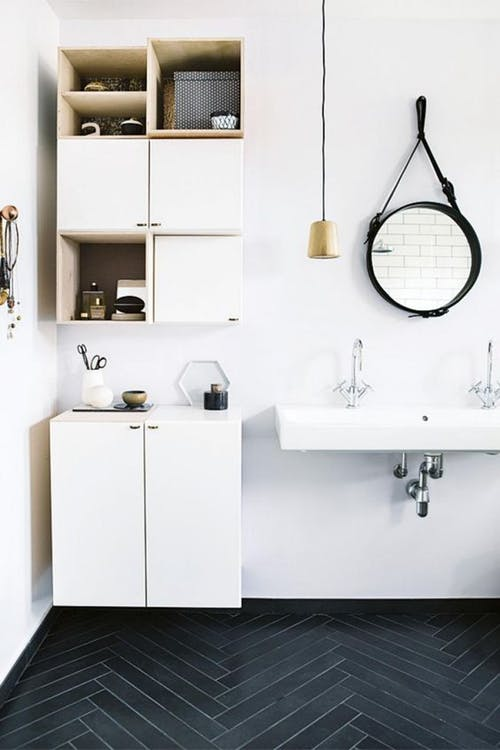 herringbone tile floors in black floating bathroom cabinets in white wall mounted bathroom sink in white white walls black framed wall mirror in round shape