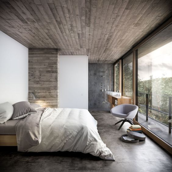 minimalist bedroom design wood board ceilings white walls with wood siding wall accents gray bed linen with white comforter concrete floors gray chair in modern style mid century modern console table