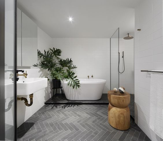 modern minimalist bathroom design modern white bathtub medium size houseplant on pot gray herringbone tile floors wall mounted sink in white wooden stool