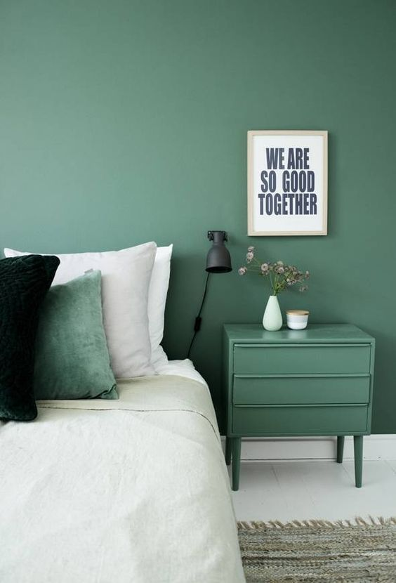 muted green wall paint muted green bedside table white bedding treatment colorful pillows
