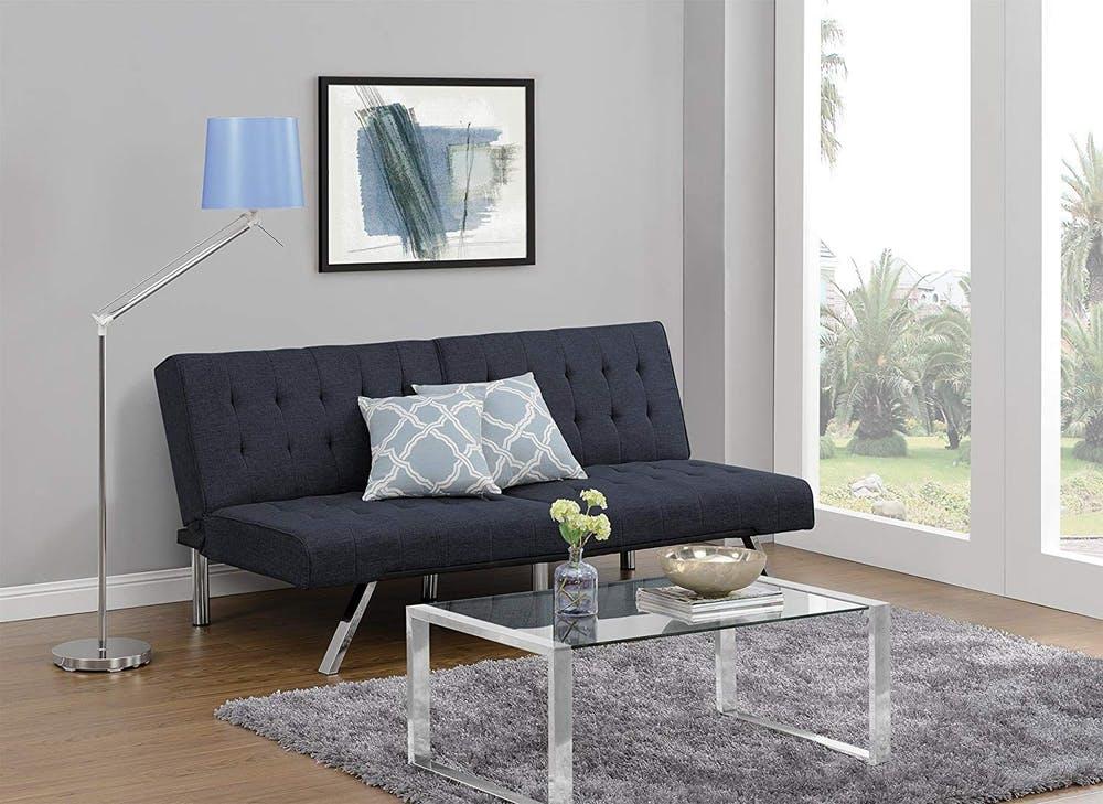 navy blue futon couch with tufted upholstery surface and chrome legs acrylic coffee table chrome floor lamp with blue lampshade gray shag rug