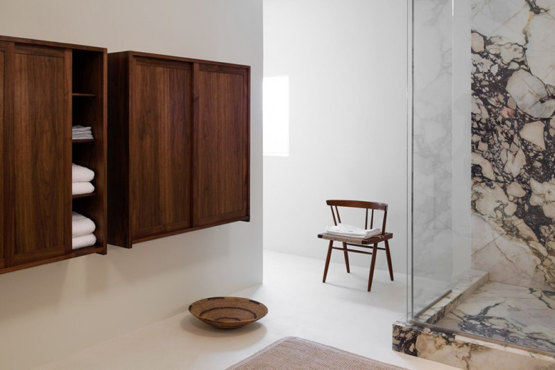 open concept bathroom scandinavian style wood chair walk in shower with clear glass enclosure and marble interior hardwood closet