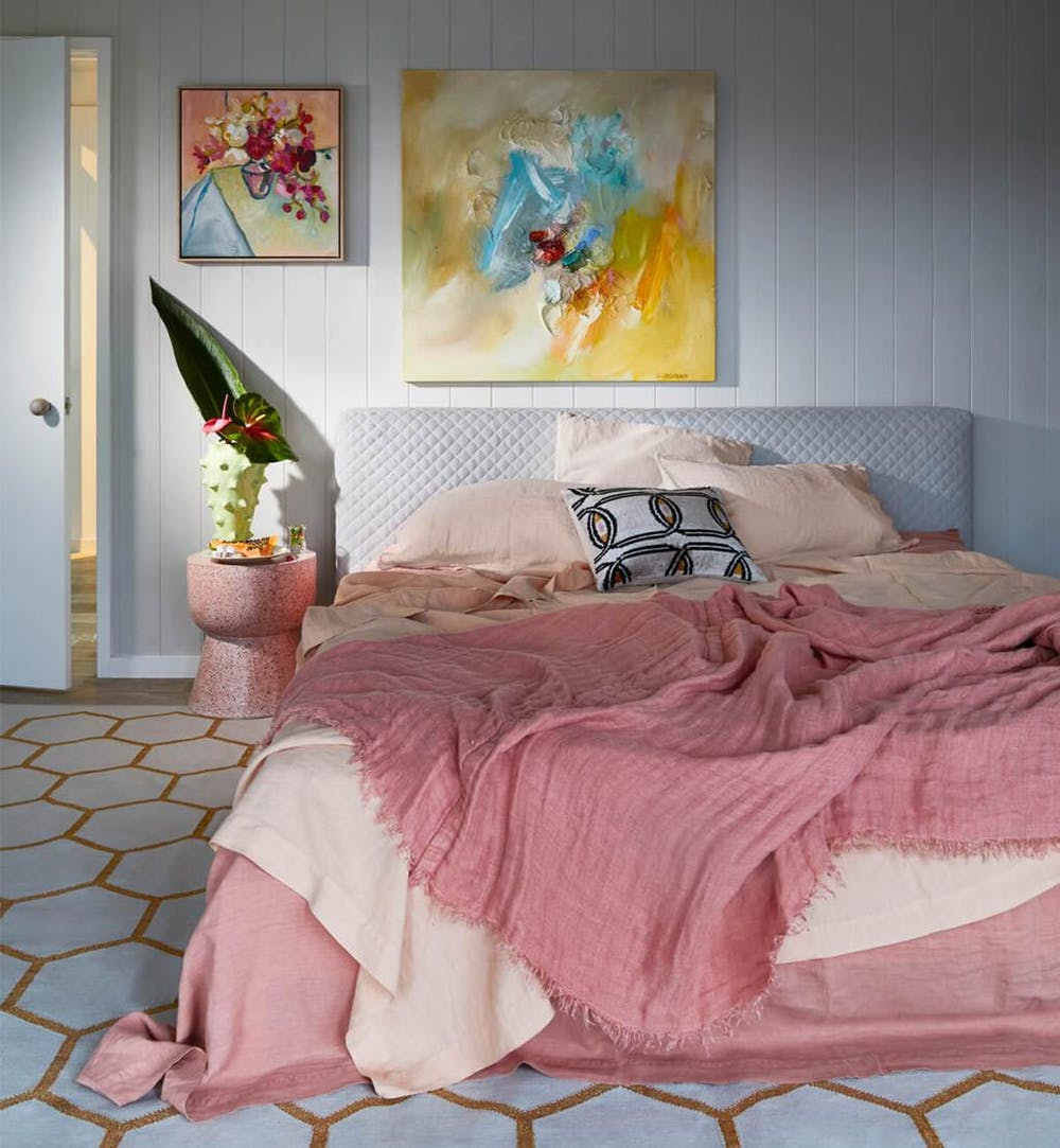 pastels & pink bedding product textured white headboard hexagon shaped tile floors colorful abstract painting pink bedside table