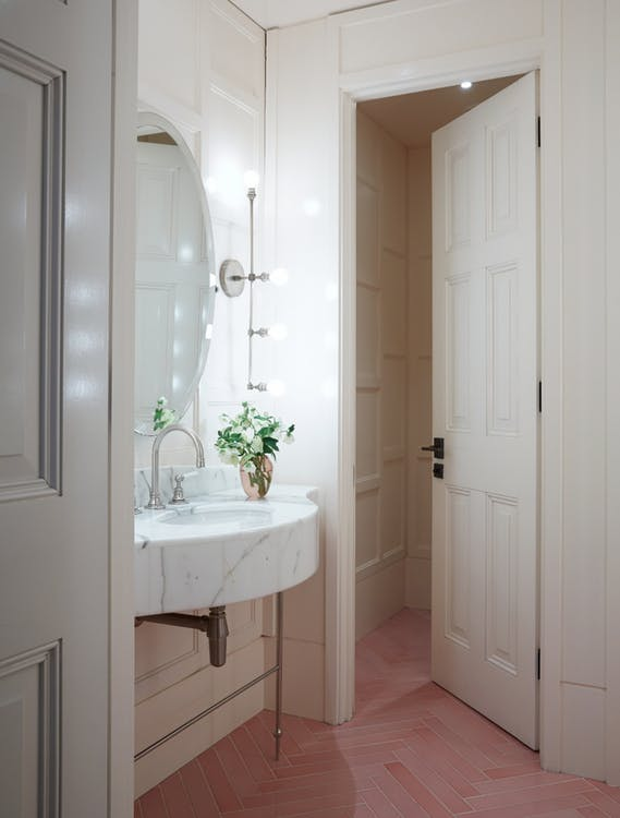 pink herringbone tile floors marble sink in white oval shaped vanity mirror with white frame