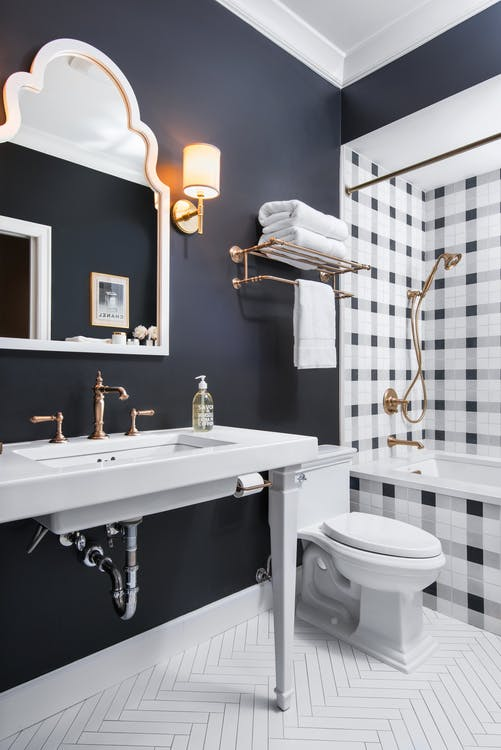 plaid tub's tiling idea white toilet bathroom sink white framed wall mirror herringbone patterned tile floors in white doff black wall