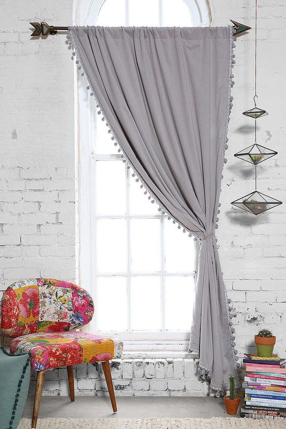 reading corner design muted gray curtains arrow shaped curtain rod multicolored chair pile of book collection white brick walls